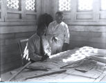[Interior designers working on sketches inside the Lama Temple.]
