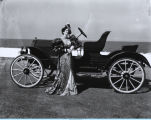 Woman in period costume standing next to a Ford Model T