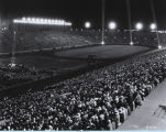 [A large crowd gathers at Soldier Field to listen to a marching band.]