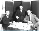 [Three unidentified men looking over the diorama of the Century of Progress Belgian Village.]