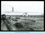 [A photograph of an unidentified building next to a rail car with construction materials nearby.]