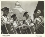 [Women in colonial American military costumes drumming in Colonial Village.] [The drummers led the...