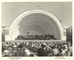 Audience view of an orchestral performance at Ford's Symphony Gardens bandshell