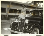 Young woman sitting on hood of a 1934 Chevrolet