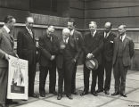 Fair dignitaries review the Century of Progress publicity poster for 1933