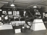 [The engine to the right is a Corliss steam engine, built ca.1884. The smaller engine on the left...