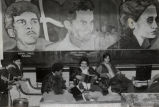 Young people sitting beneath murals of Puerto Rican political figures