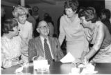 Frank Turk Sr. telling a joke to ladies at an event.