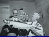 Cartoonist Charles H. Kuhn holding large fish